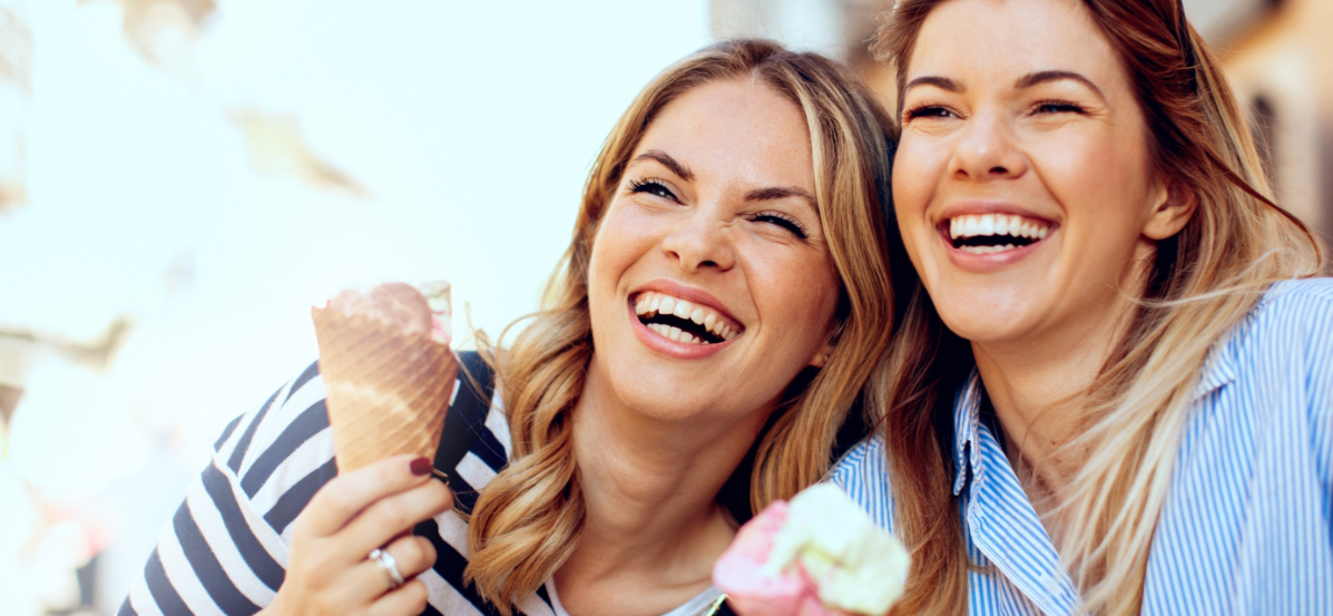 Two women laughing and eating ice cream.