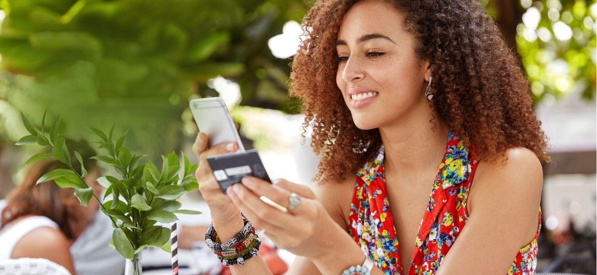 Woman with curly hair smiling as she checks her prepaid card balance on her cell phone.