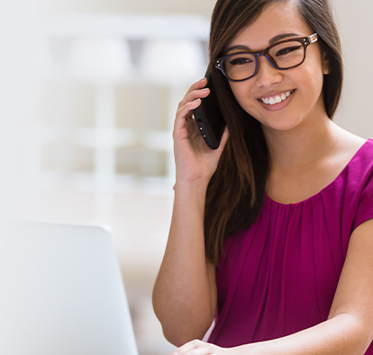 Woman with glasses, sitting in front of a desktop, while on the phone.