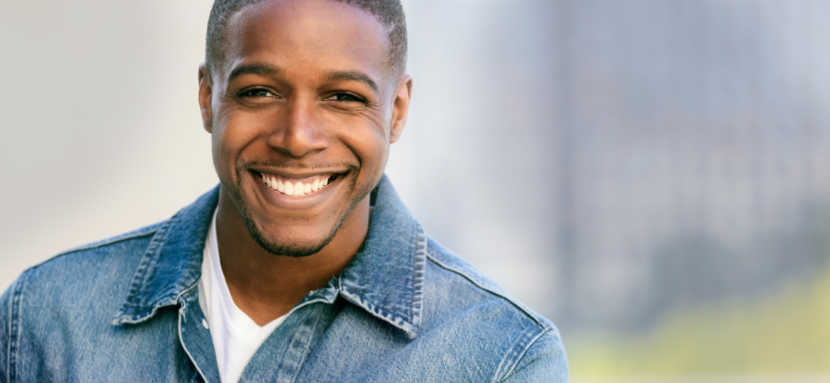 Man in a white shirt and jean jacket smiling.